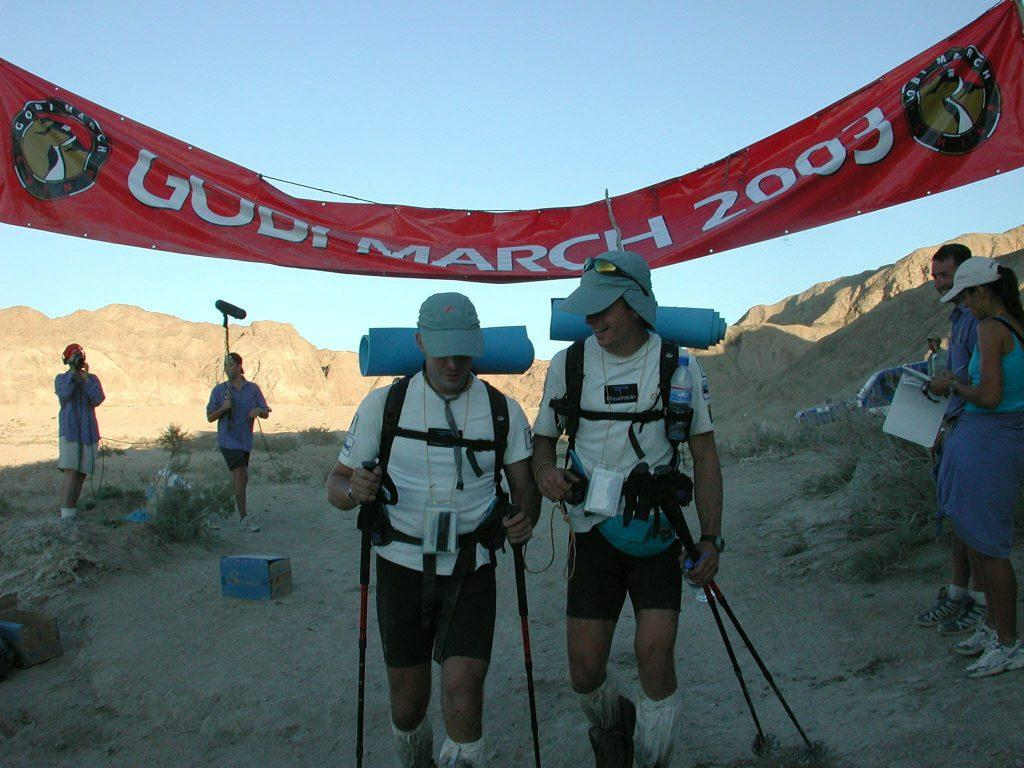 A picture of Mark and his running partner Nick Wolf at the Gobi Desert March, The Race of No Return, 2003. They are in the desert wearing backpacks and gators and peaked caps and are carrying trekking poles