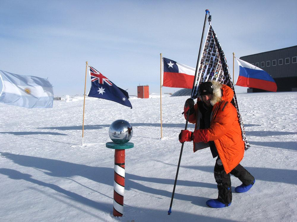A picture of Mark planting his flag of faces at the South Pole, with other national flags in the background framed by the snow