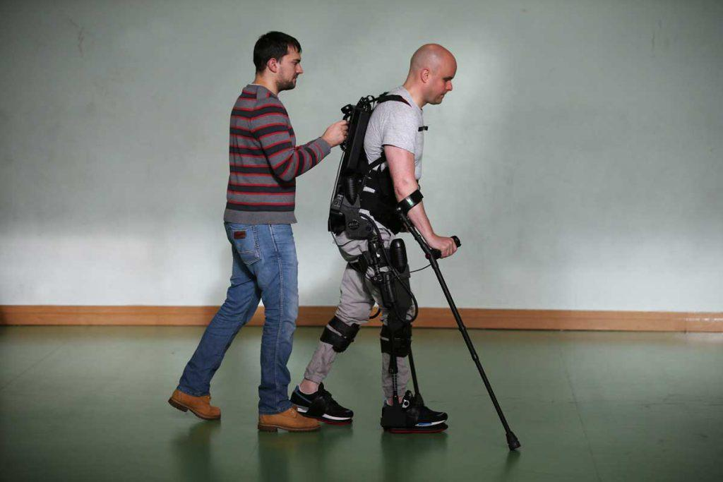 A picture of Mark walking in Ekso Bionics robotic legs in Trinity College Dublin